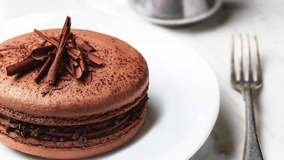 Delight in a fresh, handmade chocolate macaron with chocolate topping drizzled tableside.