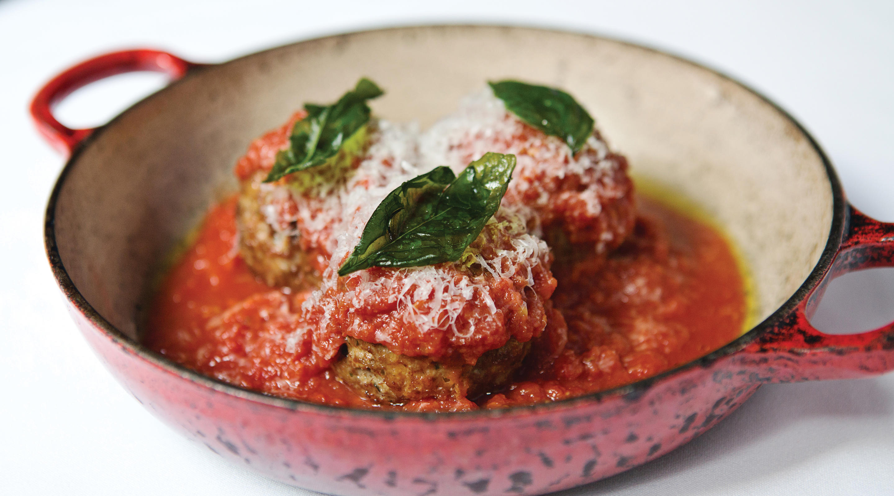 Meatballs topped with grated cheese and basil.