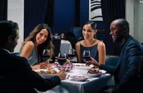 A group of four people dining in a blue room.