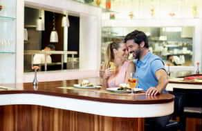 Couple enjoy eating at the restaurant counter bar.