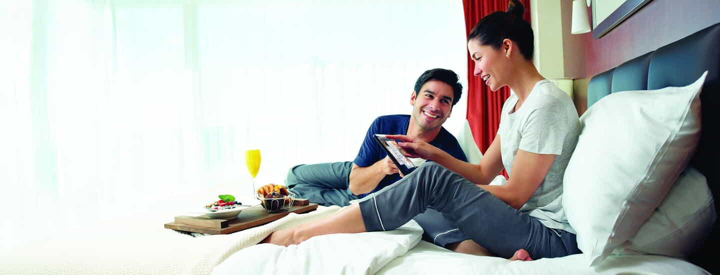 Couple using the in-room tablet while relaxing in bed with room service breakfast.