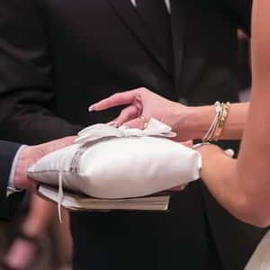 A couple taking their rings from the pillow.