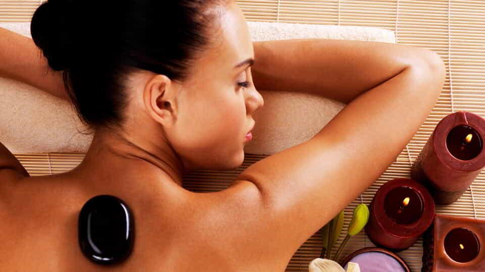 Adult woman relaxing in spa salon with hot stones on body.