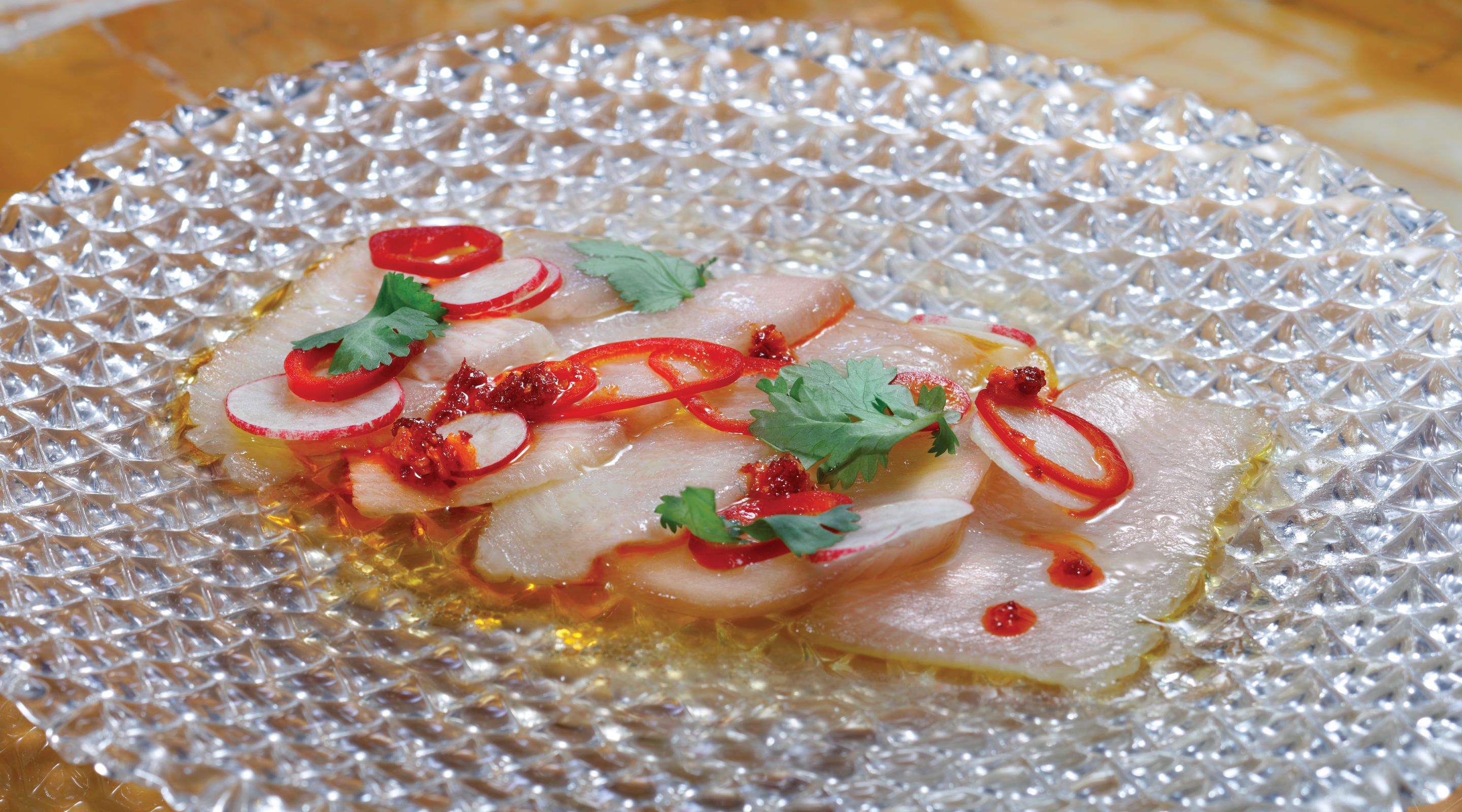 A hamachi dish with garnishes at Mayfair Supper Club.
