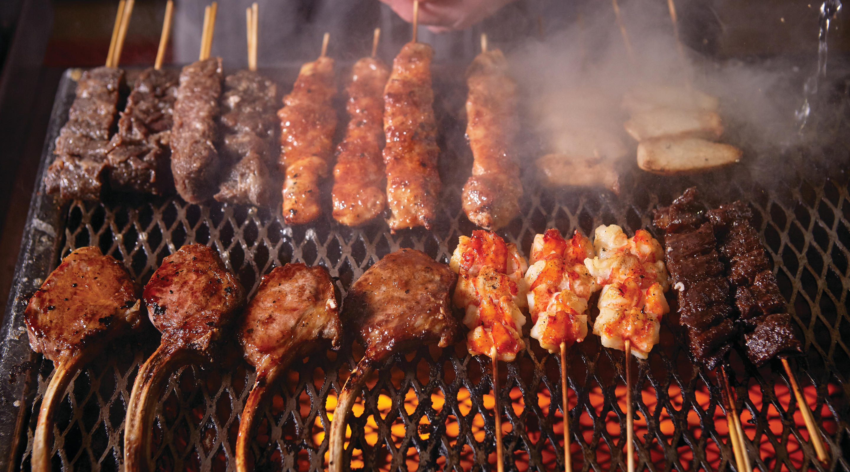 Japanese style barbecued meats being cooked.