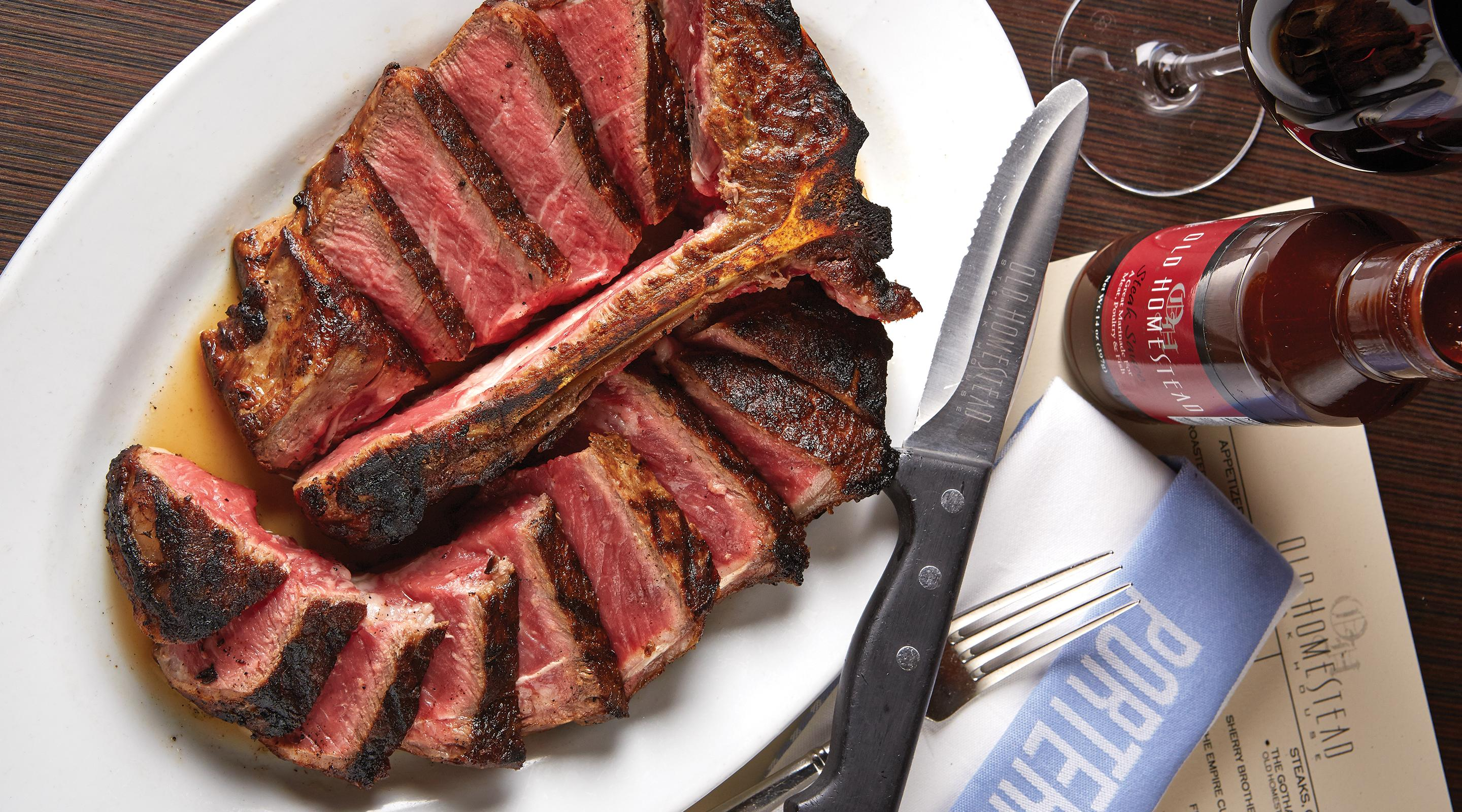 Porterhouse steak for two with sauce and a glass of red wine.