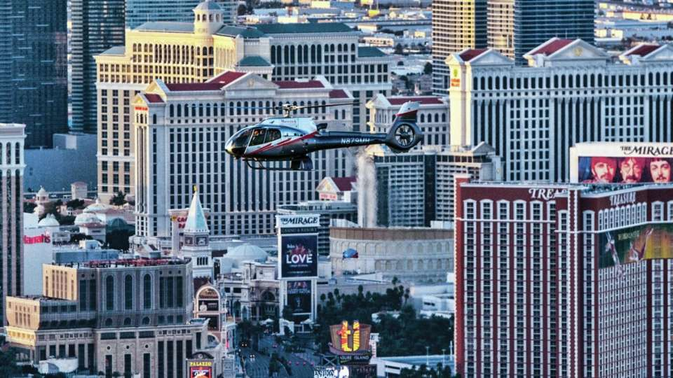 Maverick Helicopter flying over the Las Vegas Strip by day.