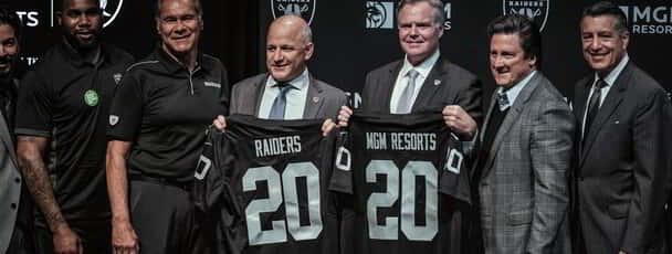 Photo of Jim Murren, Brian Sandoval, and others holding up MGM Resorts and Raiders #20 jerseys.