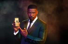 MGM Resorts BetMGM Jamie Foxx Boxing King of Sportsbooks holding a BetMGM mobile app.