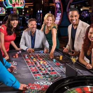 Group smiling and playing a roulette table game.