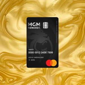 M life Rewards Mastercard on gold swirl background.
