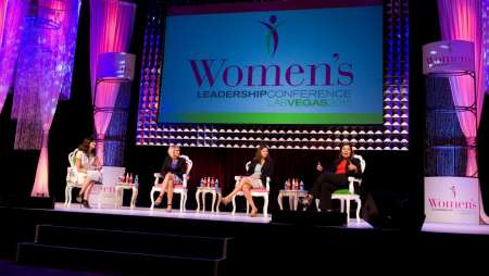 Four panelists speaking on stage at the Women's Leadership Conference.