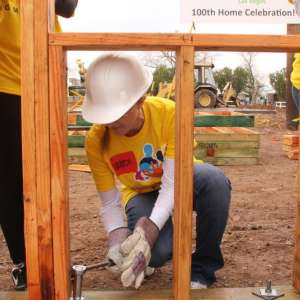 A group of volunteers aid in the construction of a local home at Habitat for Humanity.