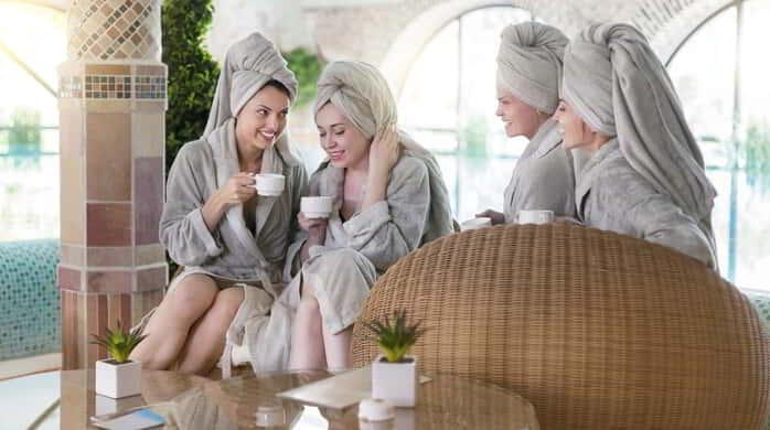 Four young happy women drinking tea at spa resort.