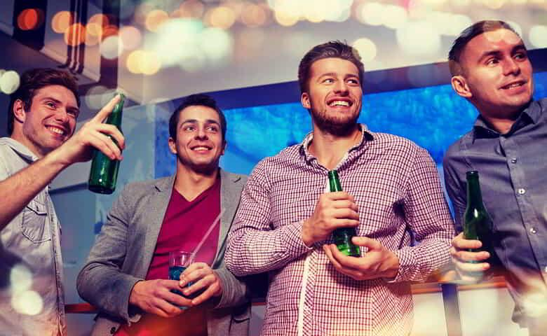 Group of male friends with beer in nightclub.