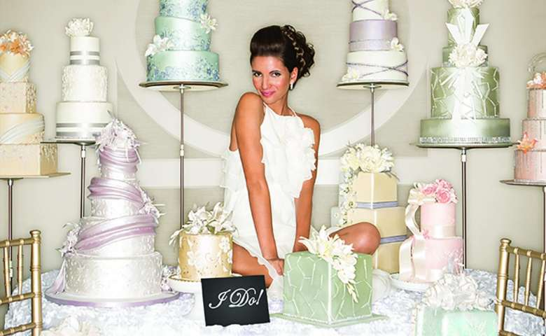 A bride sitting on a table surrounded by wedding cakes.