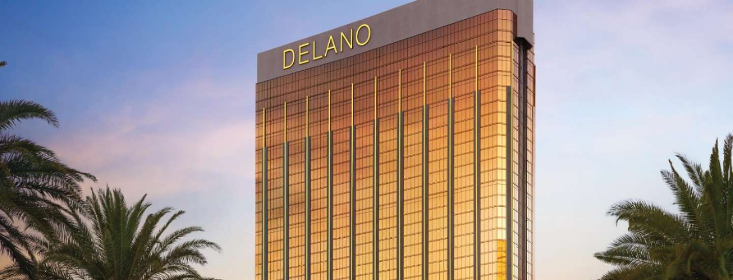 Delano Las Vegas building behind palm trees at sunset.