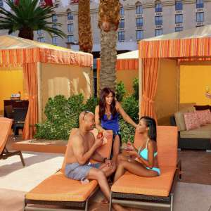 This is the first lifestyle image of a group enjoying themselves in their Excalibur Adult Pool Cabana.