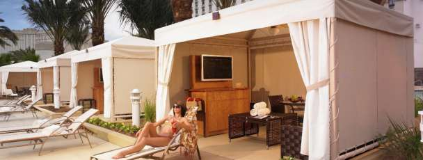 Woman lounging in a cabana at the Excalibur Pool.