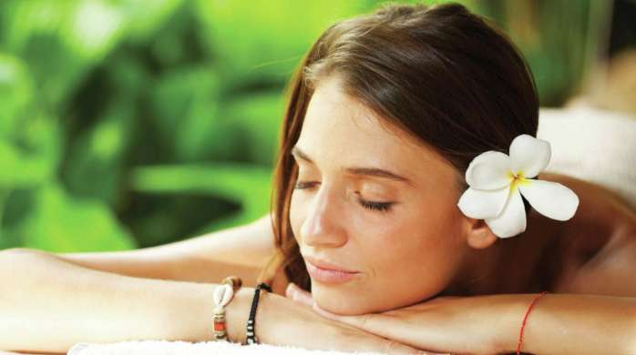 This is an image of a woman at the spa wearing a plumeria flower.
