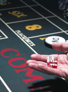 This is an image of someone rolling dice at a craps table game.