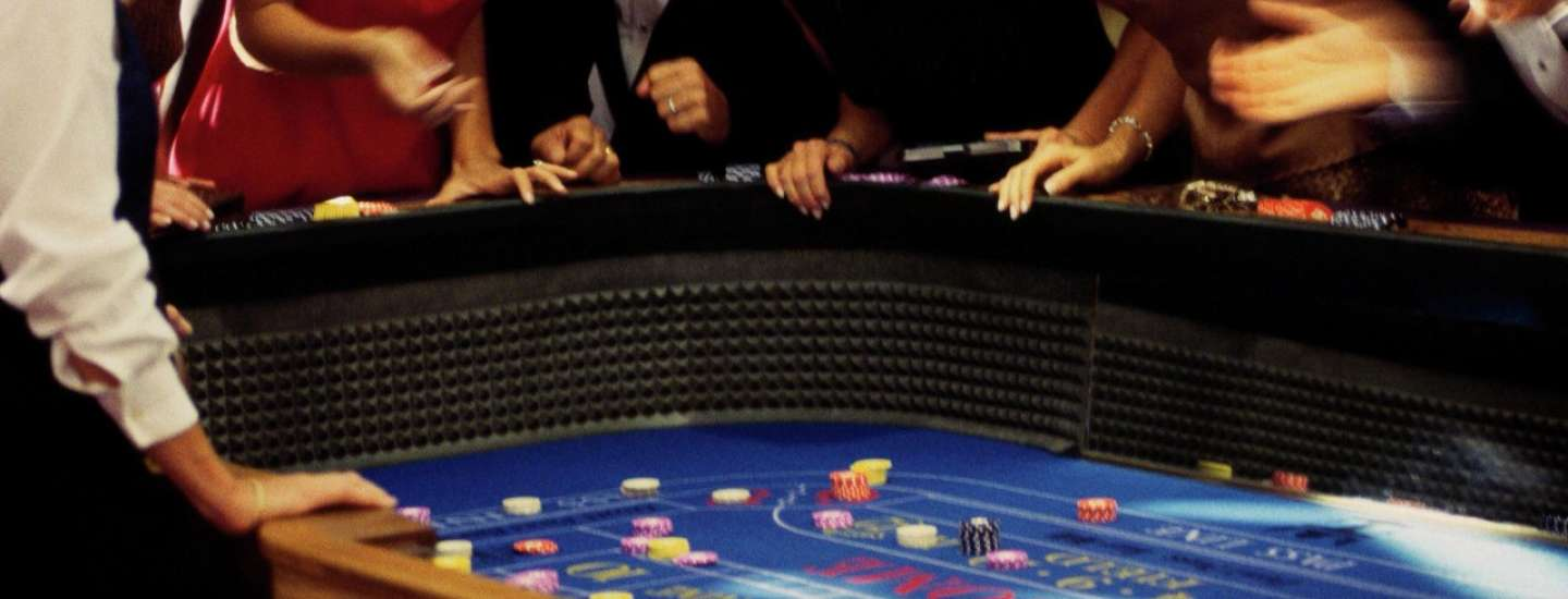 This is an image of a group of people playing at a craps table game.