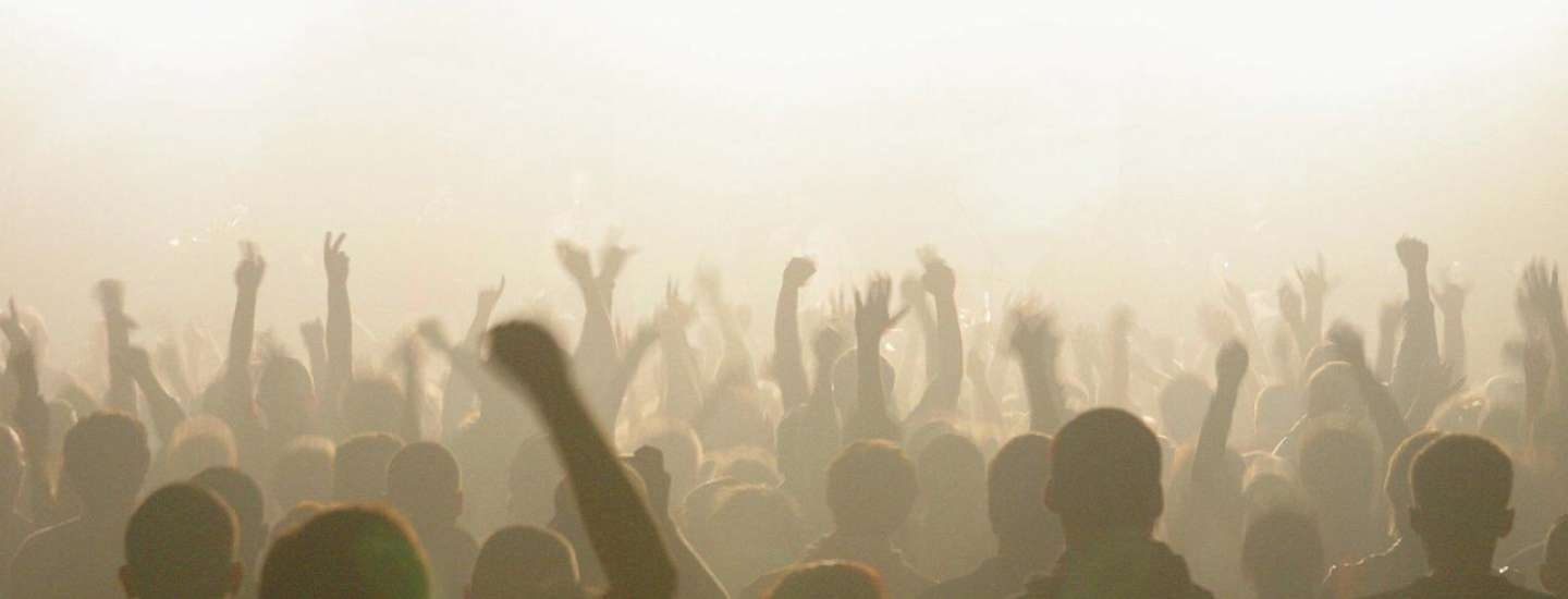 A hazy shot of concert goers with their hands in the air.