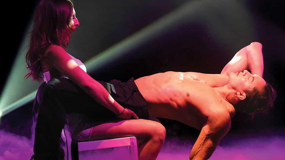 A seated woman receives a lap dance from a male performer.