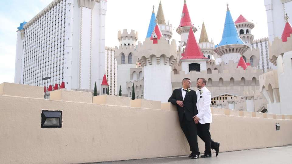 Newlywed couples shot with the Excalibur hotel background.