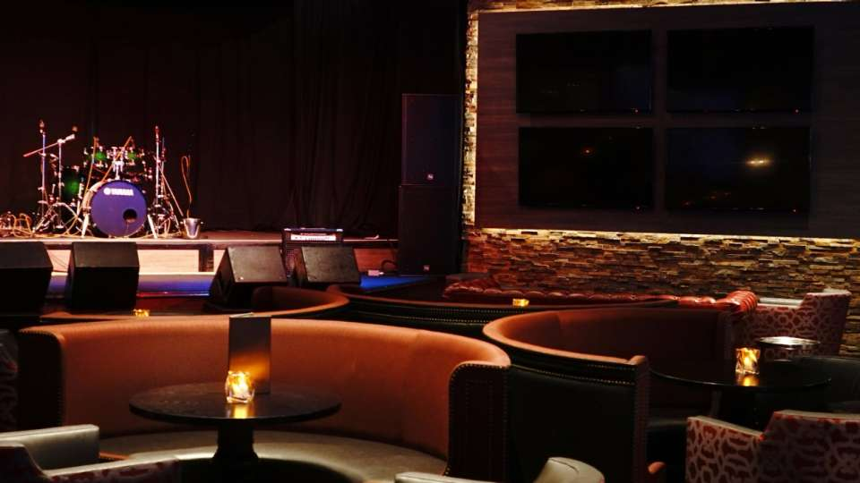 The Lounge architectural shot with live music stage and TVs.