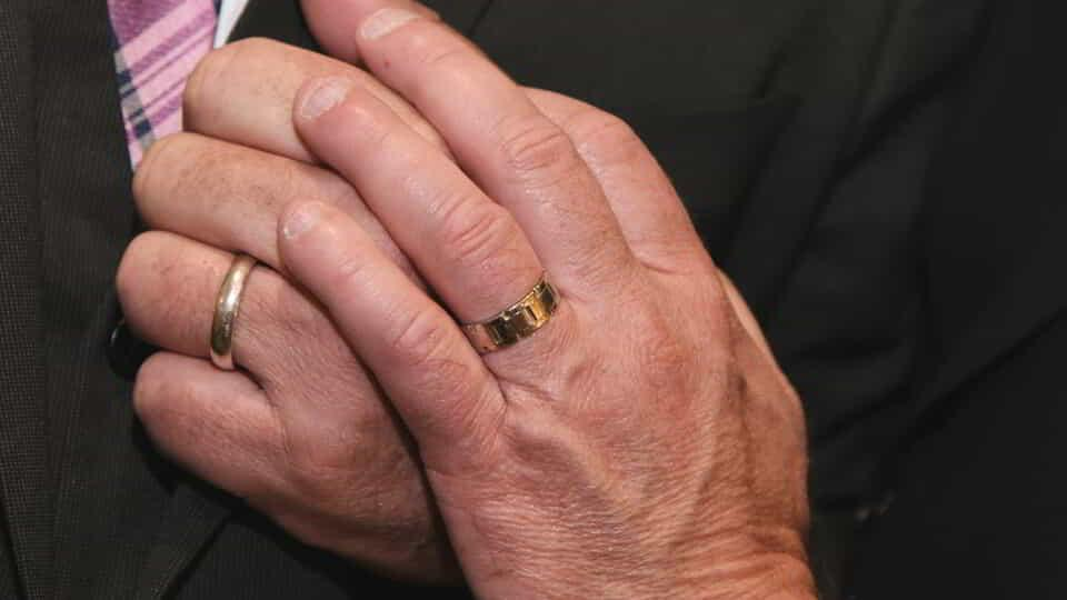 Picture of hands with wedding rings.