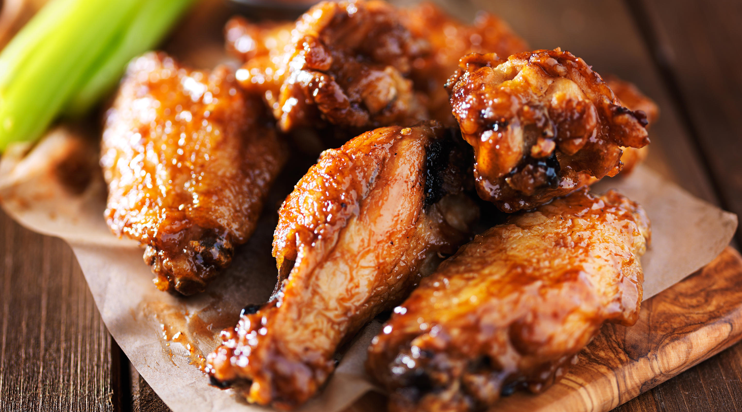 Barbecue chicken wings close up on wooden tray.