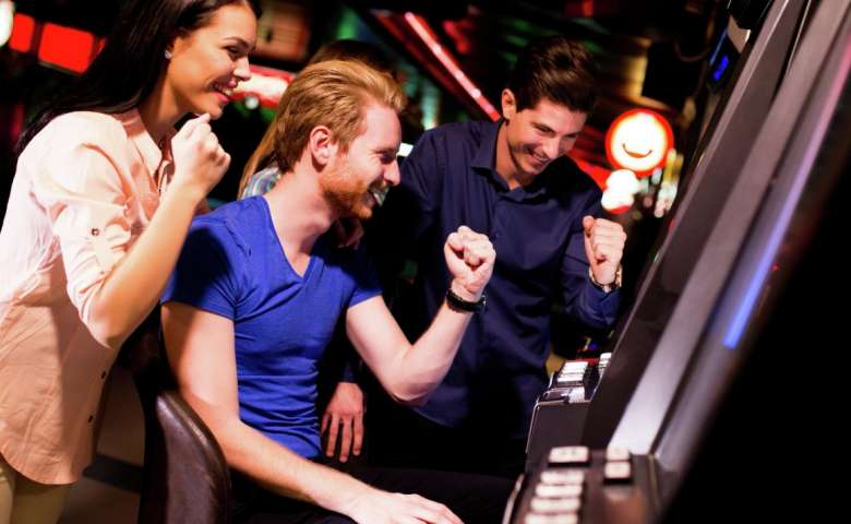 A young group of people playing slots.