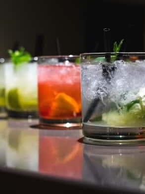 Several flavored mojitos on a bar.