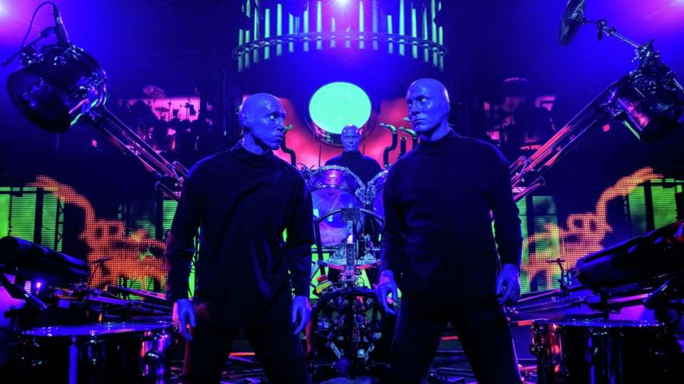 Blue Man Group posing in front of a drumset during a performance in Las Vegas.