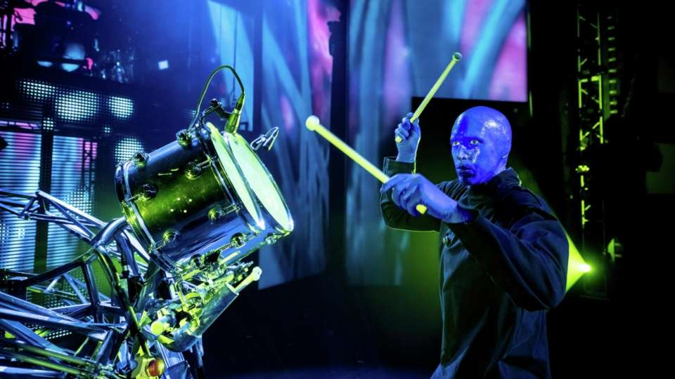 Blue Man Group member plays the drums in front of an LED screen.