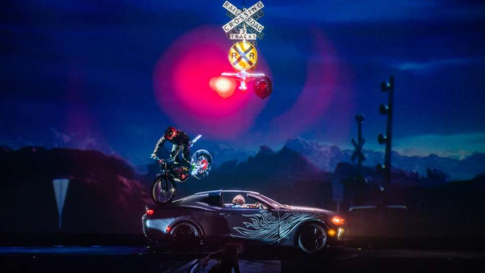 A motorcycle jumping a car in R.U.N produced by Cirque du Soleil.