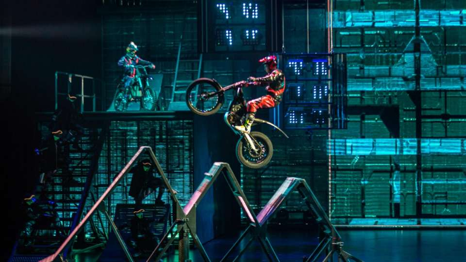 A motorcycle going over a triple ramp in R.U.N produced by Cirque du Soleil.