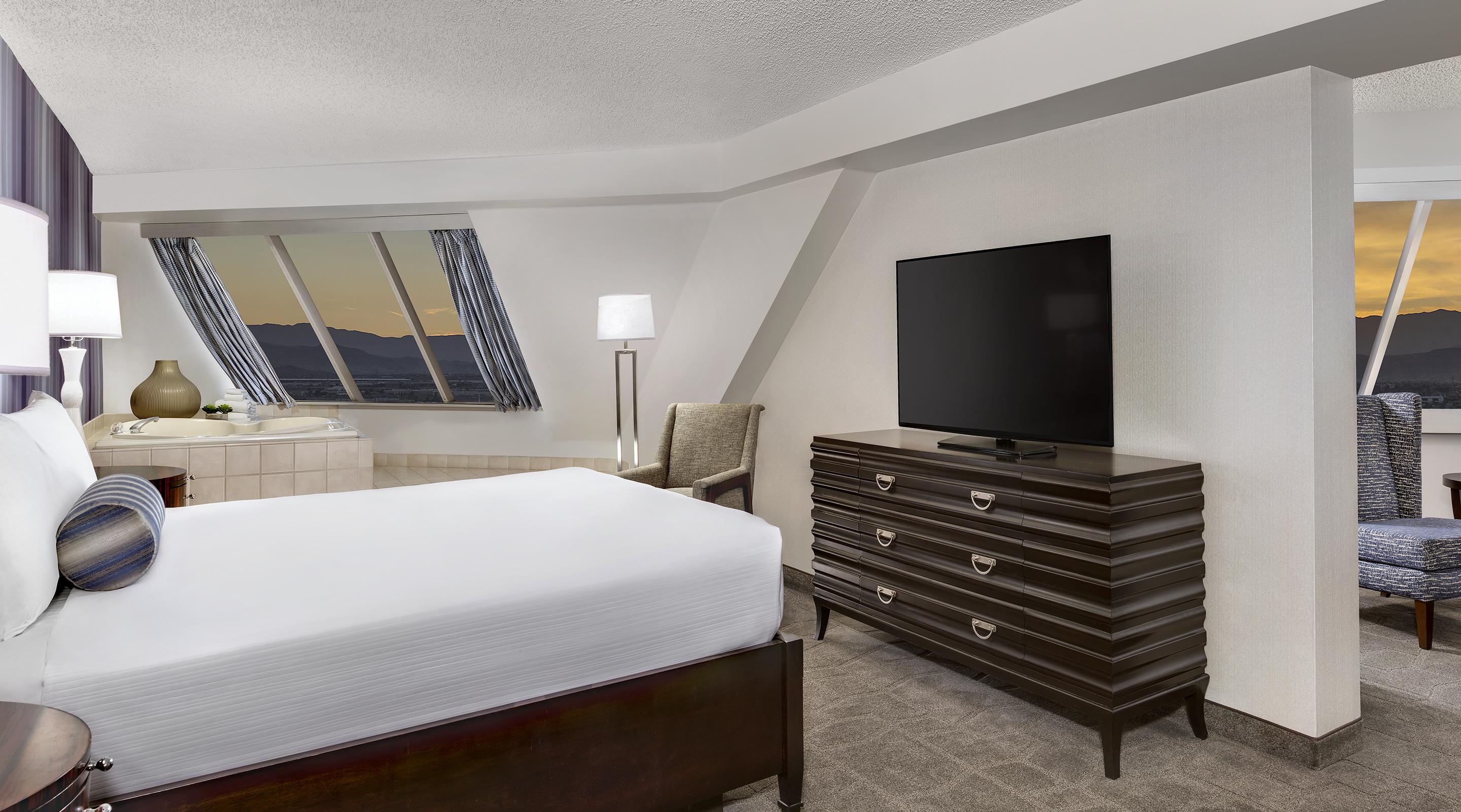King bed, TV and and soaking tub in the Pyramid Premium Corner Suite.