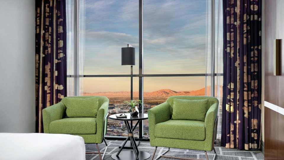 Two chairs in living area with a mountain view in a Tower Premium King Room.