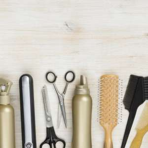Hairdressing tools on wooden background with copy space at top.