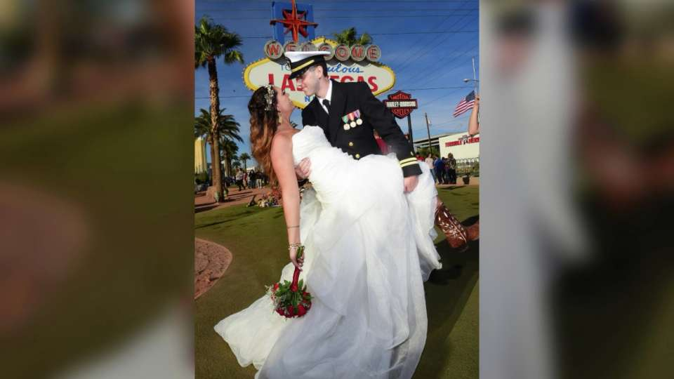 Couple outdoor wedding in front of Las Vegas sign.