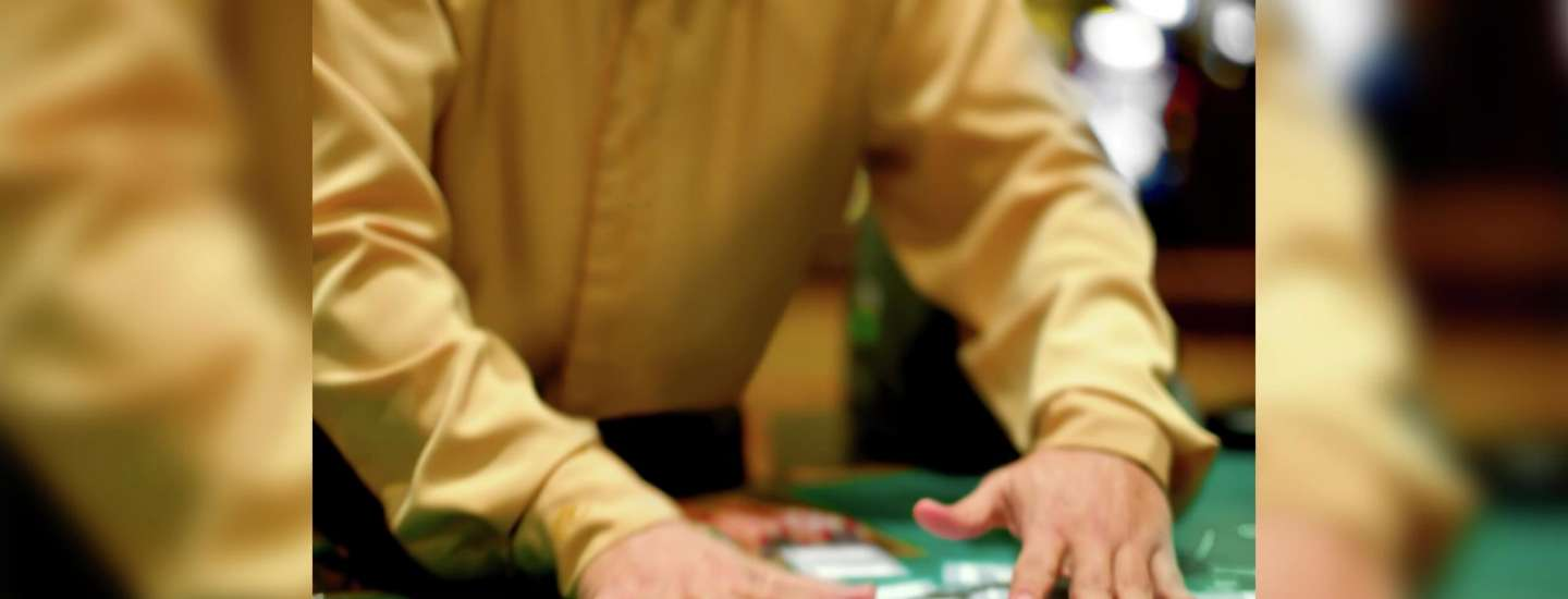 A dealer collects cards off the poker table.