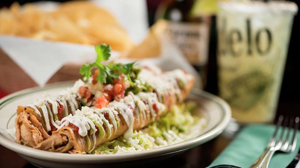 Hussong's Cantina Flauta; Corn Tortillas Packed with Seasoned Pulled Chicken Over a Lettuce-Cabbage Mix, Topped with Red Tomato Salsa, Tomatillo-Avocado Salsa, Pico De Gallo, Guacamole, Cotija Cheese, and Sour Cream