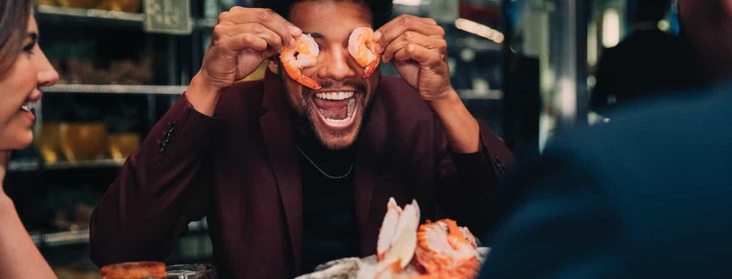 Group of people eating shrimp and laughing.