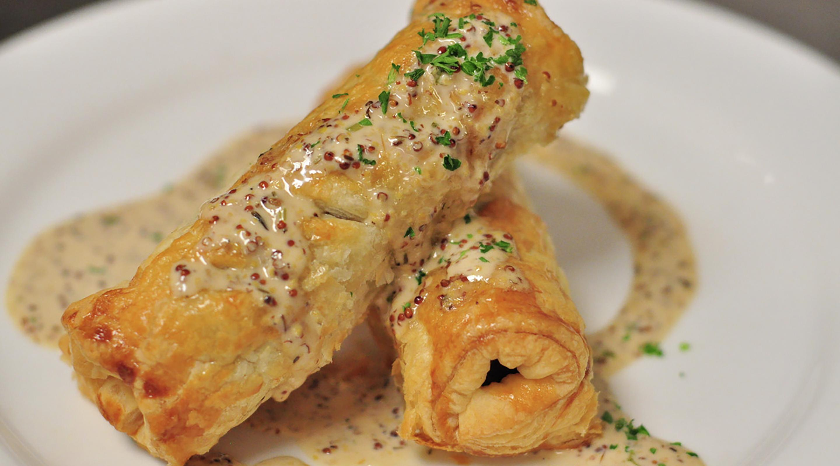 Pastry wrapped bangers, guinness mustard sauce, fresh herbs