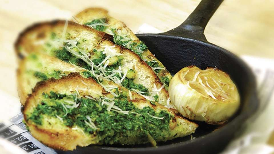 Slice of Vegas Not Your Momma's Garlic Bread; Italian Bread Infused with Roasted Garlic Topped with Olive Oil and Basil Pesto, Accompanied with a Roasted Garlic Head