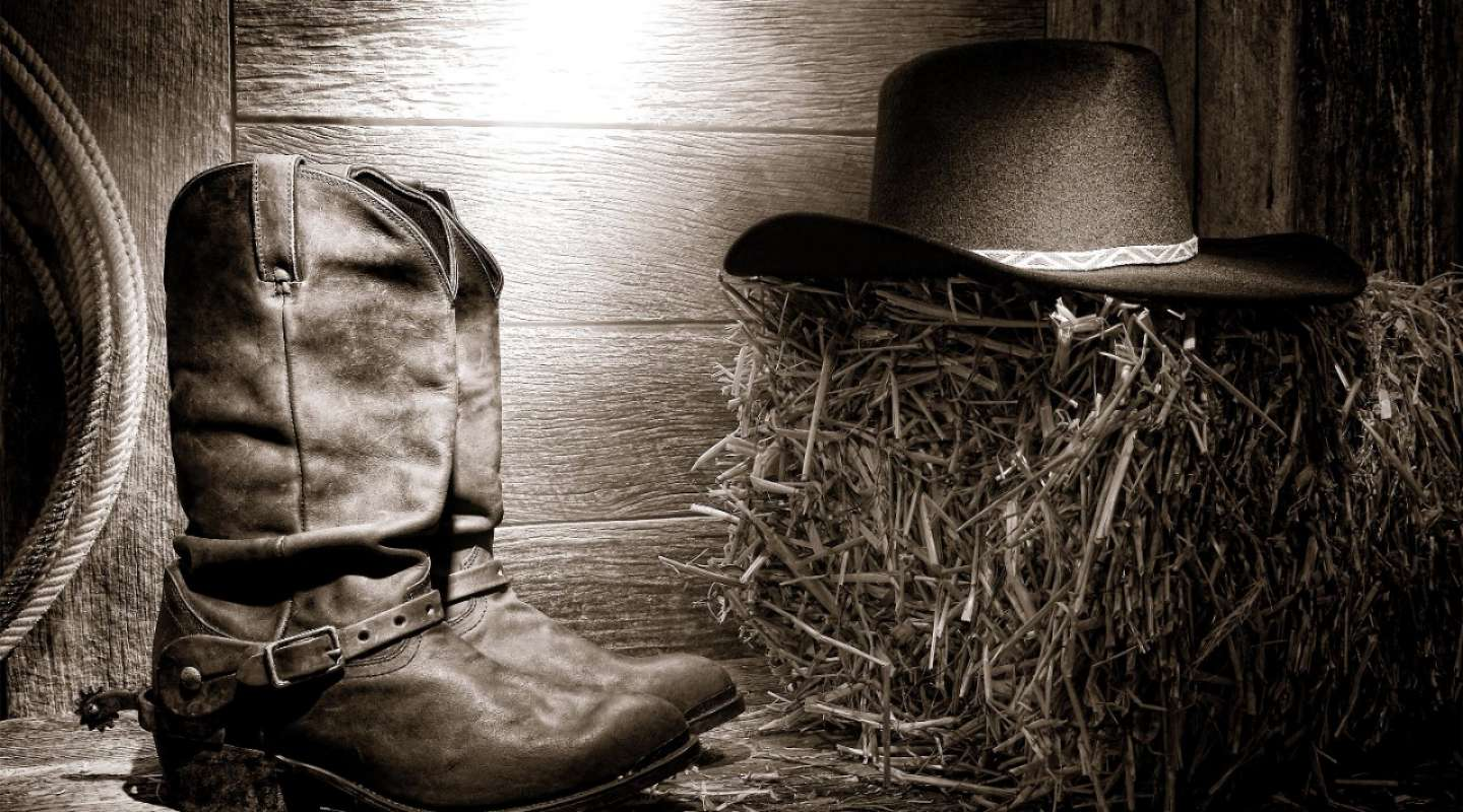 WNFR cowboy boots and hat under a spotlight.