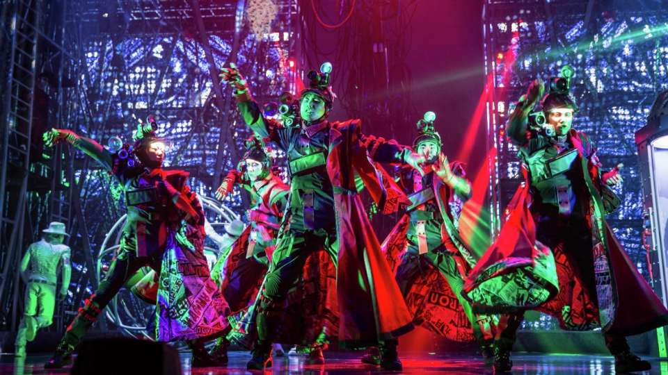 A group of dancers perform on stage with red and green lights.