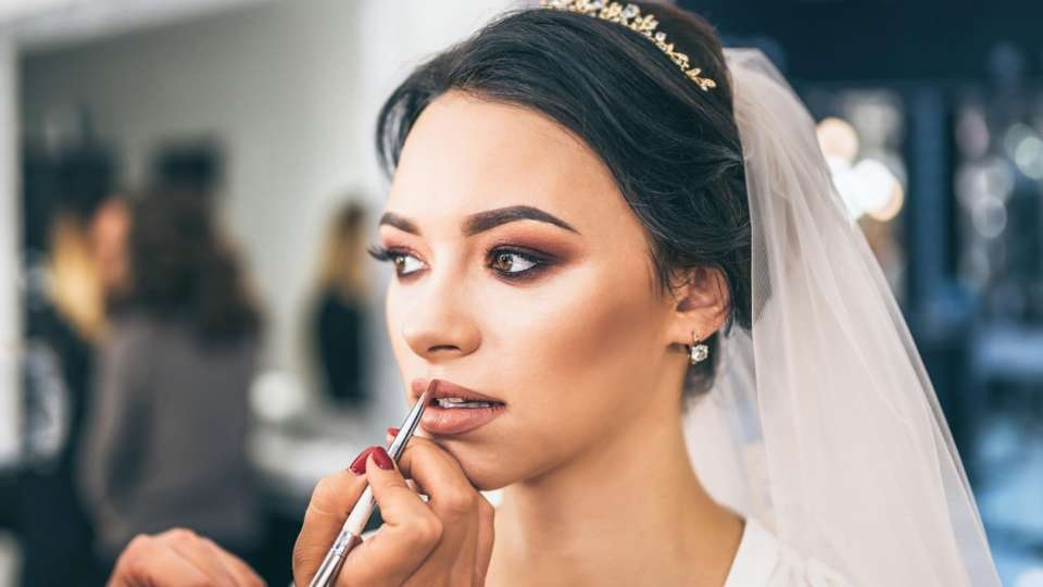 Make-up is being applied to the bride.